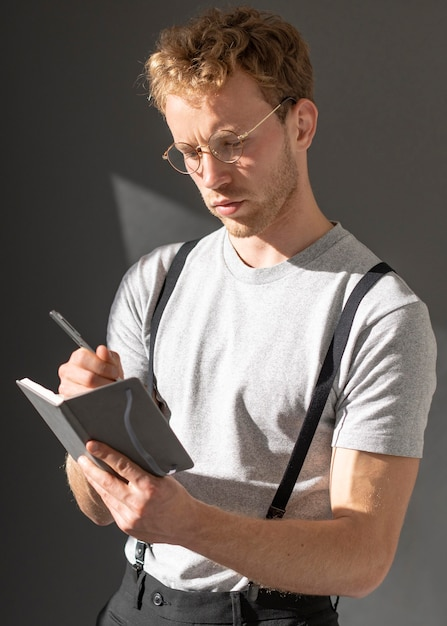 Male model wearing suspenders accessory and writes Free Photo