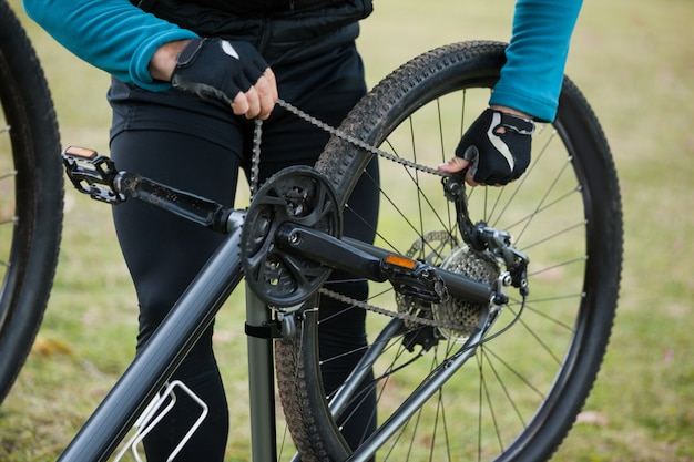 Мужской горный байкер чинит велосипедную цепь Premium Фотографии