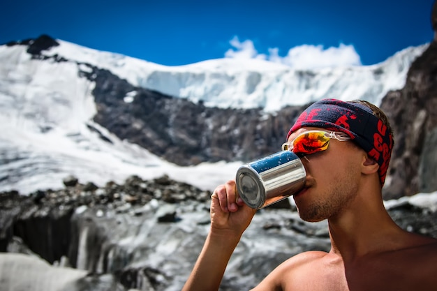 Male mountaineer drinking water from a mug on a glacier in the mountains travel lifestyle concept active vacations Premium Photo