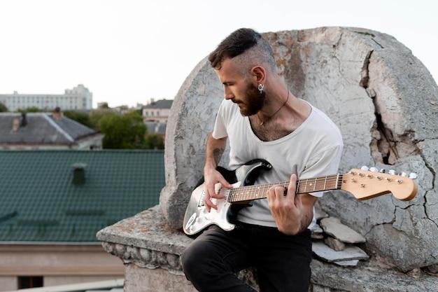 屋上のエレクトリックギターを演奏する男性ミュージシャン 無料写真