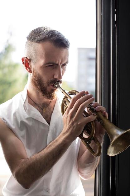ウィンドウの横にあるコルネットを演奏する男性ミュージシャン 無料写真