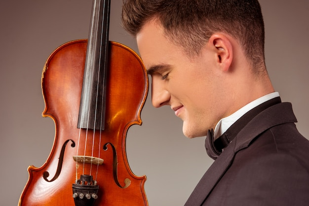 Male musician stands with a violin. Premium Photo