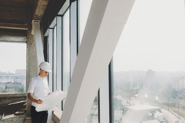 건설중인 그의 건물의 큰 창 근처에서 계획을보고있는 남성 소유자. 프리미엄 사진