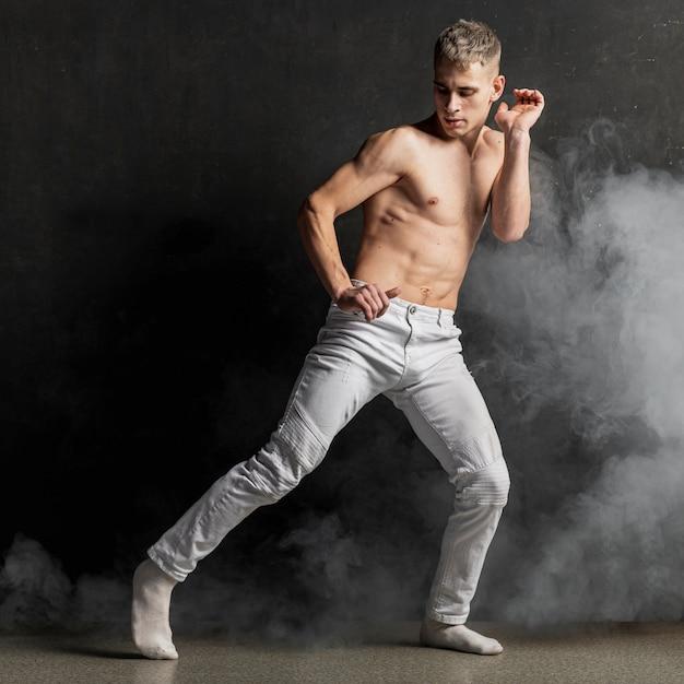 Мужской исполнитель позирует в джинсах с носками и дымом Бесплатные Фотографии