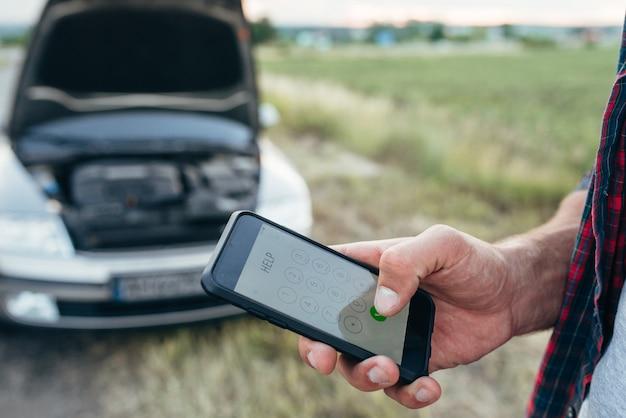 Рука человека мужского пола с телефоном, сломанная машина с открытым капотом. проблема с автомобилем, аварийная служба Premium Фотографии