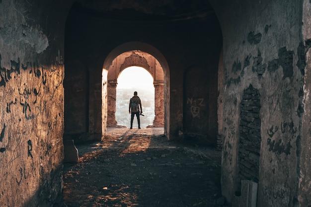 古い放棄された建築のアーチに立っている男性のカメラマン 無料写真
