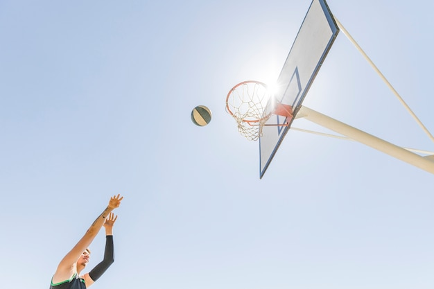 A male player throwing basketball in the hoop against clear blue sky Free Photo