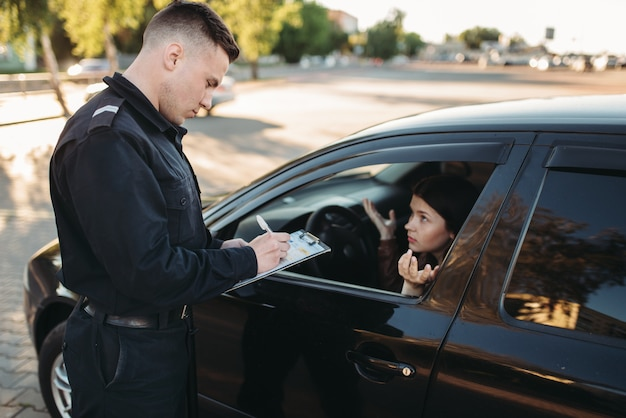 Полицейские-мужчины проверяют автомобиль на дороге Premium Фотографии