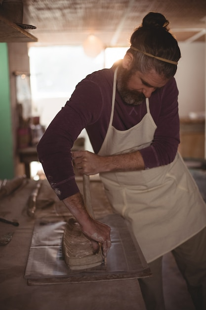 Male potter designing clay with stick Premium Photo