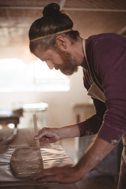 Male potter designing clay with sticks Premium Photo