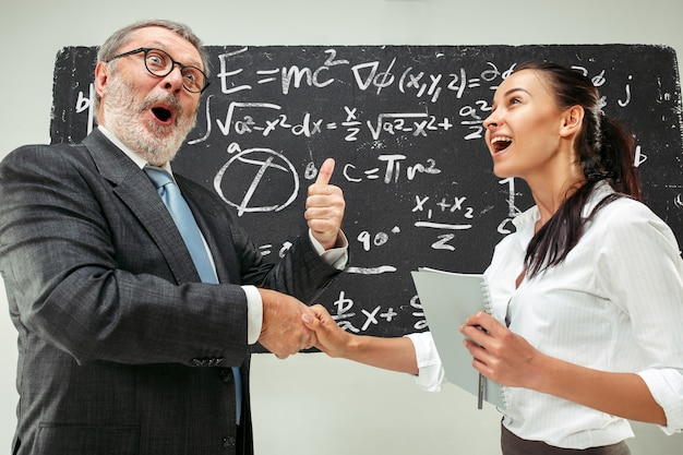 Male professor and young woman against chalkboard in classroom Free Photo