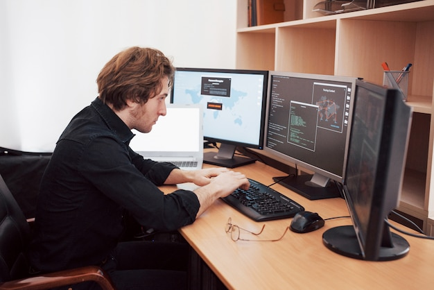 Male programmer working on desktop computer with many monitors at office in software develop company. website design programming and coding technologies Premium Photo