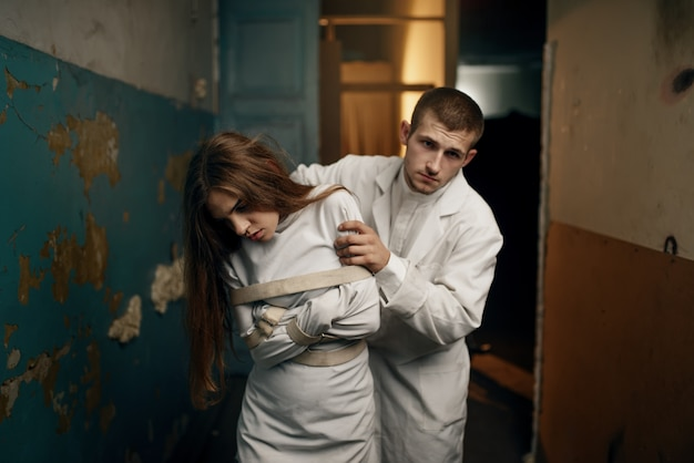 Male psychiatrist leads crazy female patient in straitjacket, mental hospital. woman in strait jacket undergoing treatment in clinic for the mentally ill Premium Photo