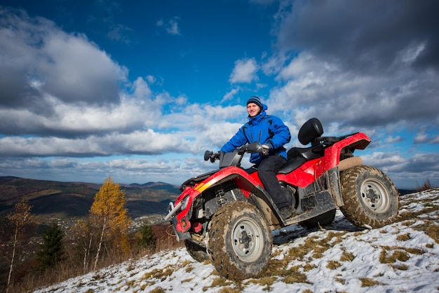 Male on the quad riding down on the snowy slope on sunny day Premium Photo