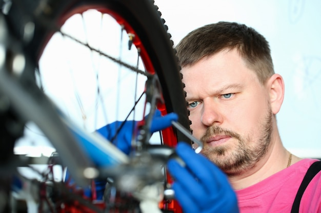 Male repair man bicycle service in blue protective Premium Photo