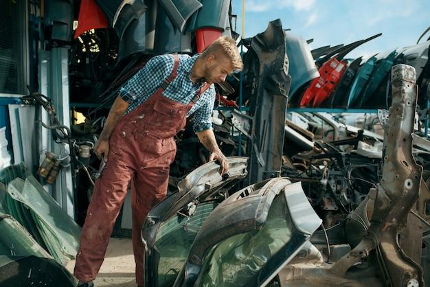 Мужчина-ремонтник выбирает запчасти на свалке автомобилей Premium Фотографии