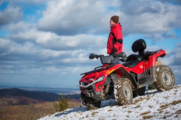 Male rider in a red winter clothes with red quad bike Premium Photo