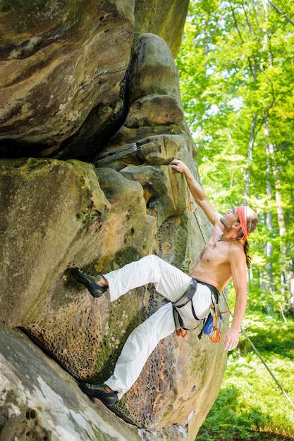 Male rock climber climbing with rope on a rocky wall Premium Photo