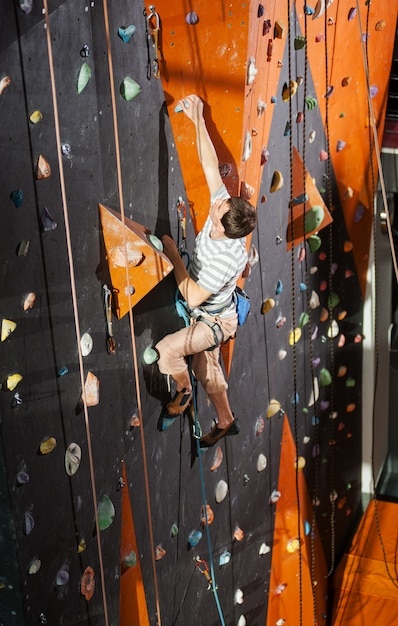 Male rock-climber practicing climbing on rock wall indoors Premium Photo