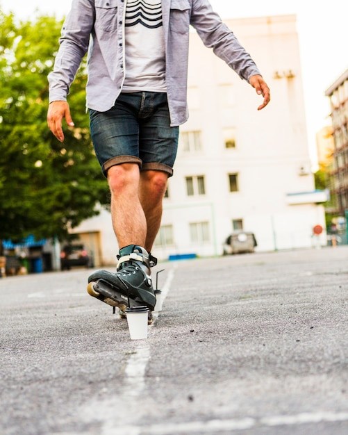 Male rollerskater's foot in front of disposal cup Free Photo