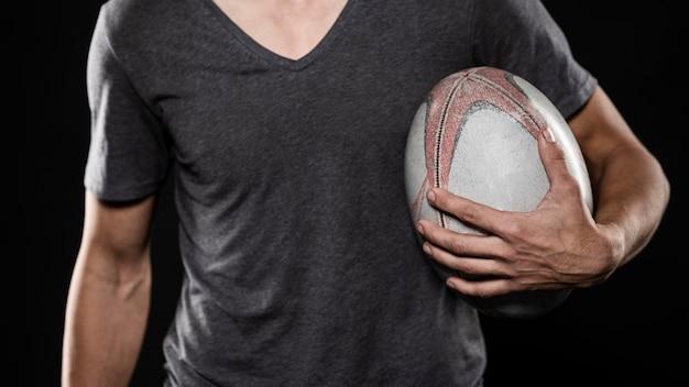 Игрок в регби мужского пола, держащий мяч Бесплатные Фотографии