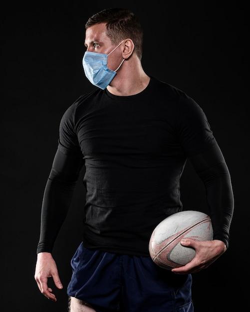 Игрок в регби мужского пола с медицинской маской и мячом Бесплатные Фотографии