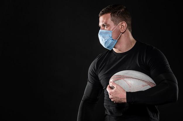 Игрок в регби мужского пола с медицинской маской и копией пространства Бесплатные Фотографии