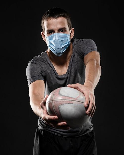 Игрок в регби мужского пола с медицинской маской держит мяч Бесплатные Фотографии