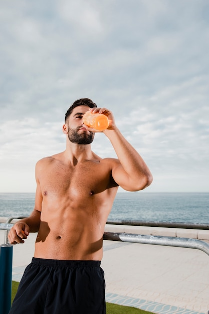 Male runner hydrating while break Free Photo