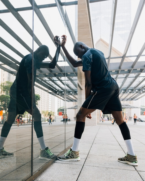 Free Photo | A male runner stretching his muscle standing in front of glass
