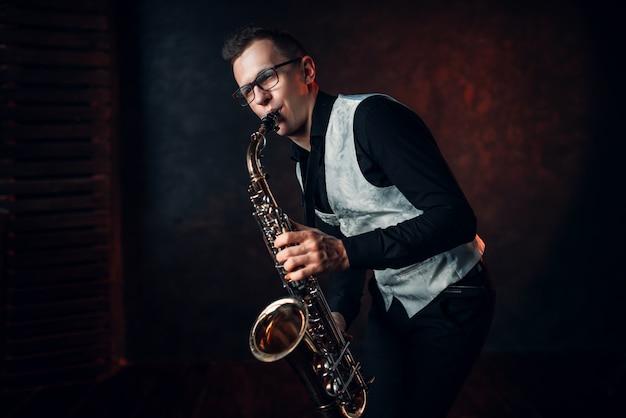 Саксофонист играет классическую джазовую мелодию на саксофоне. Premium Фотографии