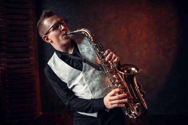 Мужской саксофонист играет классический джаз на саксофоне Premium Фотографии