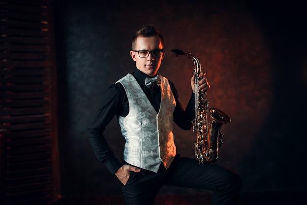 Мужской саксофонист позирует с саксофоном, джазовый человек. Premium Фотографии