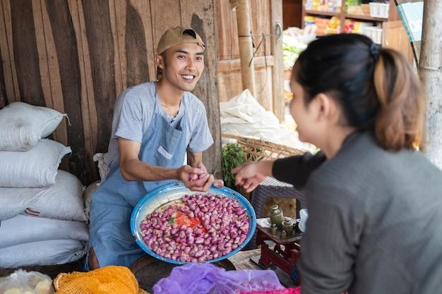男性の売り手は野菜屋で女性の買い手に仕えるためにエシャロットを拾います Premium写真
