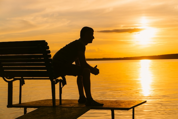 Male sits on the edge of wooden bench on footbridge in the river at sunset Premium Photo
