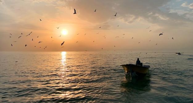 Maschio in una piccola barca a remi nel mezzo del bellissimo mare con il sole che splende Foto Gratuite