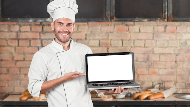Male smiling baker showing an open laptop with blank white screen Free Photo
