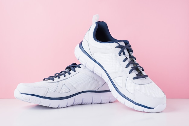Male sneakers for run on a pink background. white fashion stylish sport shoes, close up Premium Photo