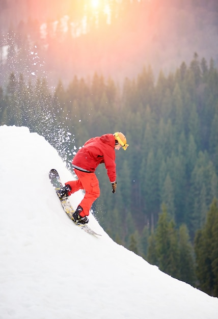 Male snowboarder freerider in a red suit riding from the top of the snowy hill with snowboard Premium Photo