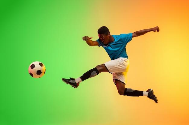 Мужской футбол, обучение футболиста в действии, изолированные на градиентной студии в неоновом свете Бесплатные Фотографии