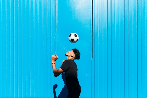 Male sportsman exercising with soccer ball against cyan wall Free Photo