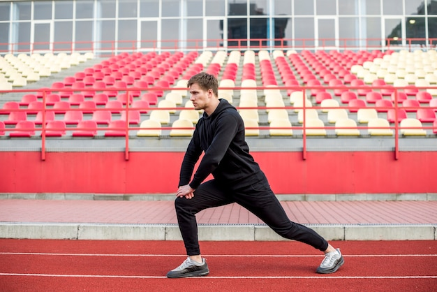 Male sportsperson exercising on race track in front of bleacher Free Photo