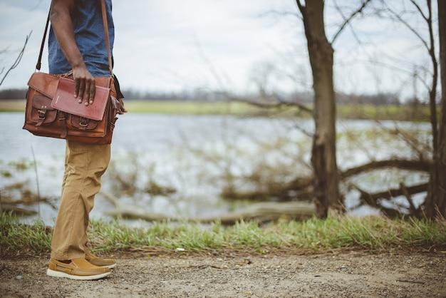Мужчина стоит возле озера, держа библию Бесплатные Фотографии