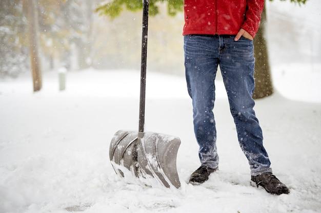 Мужчина стоит на заснеженном поле и держит лопату для снега Бесплатные Фотографии