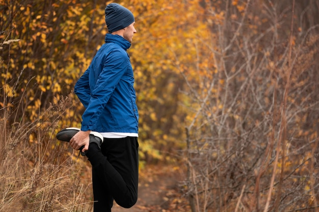 Мужчина растягивает ноги в лесу Бесплатные Фотографии