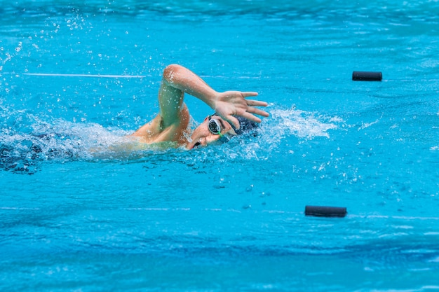 Male swimmer doing freestyle swimming stroke at a local pool Premium Photo