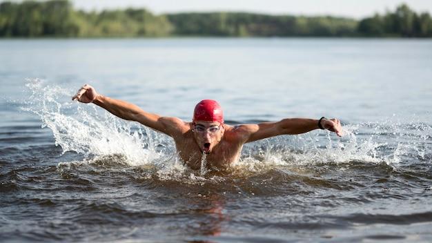 Maschio che nuota nel lago Foto Gratuite
