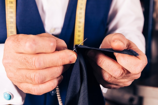 A male tailor's hand sewing the fabric with needle Free Photo
