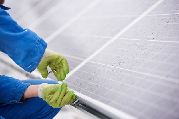 Male technician in blue suit installing photovoltaic blue solar modules with screw Premium Photo