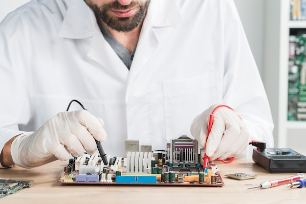 Male technician checking computer with digital multimeter on wooden desk Free Photo